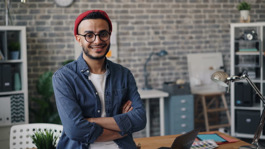 Portrait of happy business owner good-looking bearded guy standing in creative office with arms crossed smiling and looking at camera. People and workplace concept. | Shutterstock HD Video #1028622938