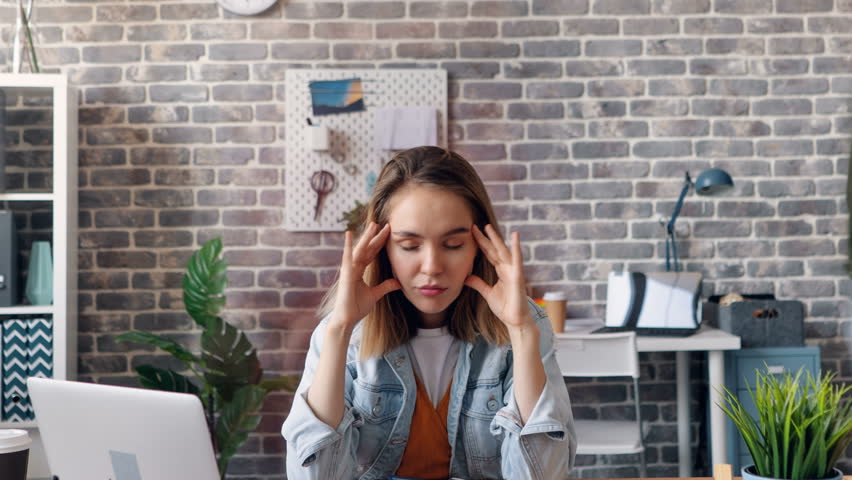 Spinning time-lapse of young woman suffering from migraine in office touching head sitting at table with closed eyes feeling headache. Youth and work concept.