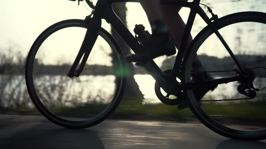 Cyclist Triathlete Twist Pedals And Riding Road Bicycle.Cycling Athlete Workout At Sunset On City Park.Gear System And Road Bike Wheel Rotation.Triathlon Cyclist Exercising Pedaling.Sport Concept | Shutterstock HD Video #1028623439