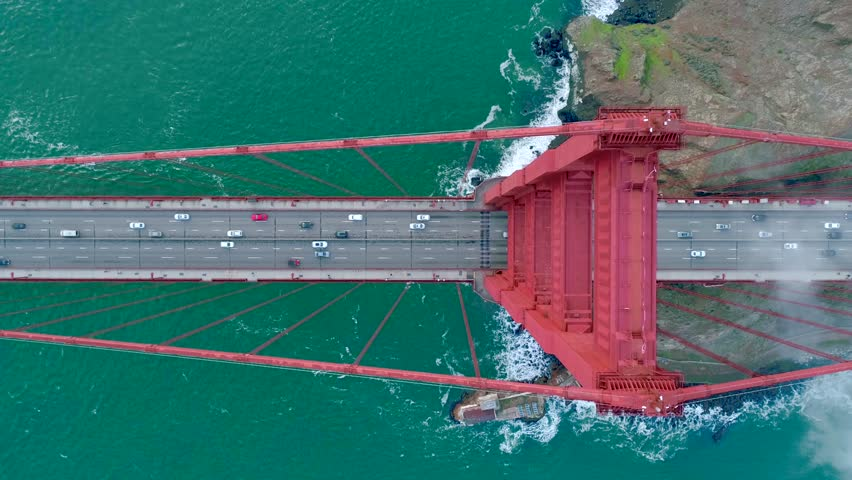 Aerial video of the Golden Gate. The busy road on the red bridge over the deep green Pacific Ocean. Fog drifting above the waves crashing the San Francisco Slow motion. California USA. Top view 4K