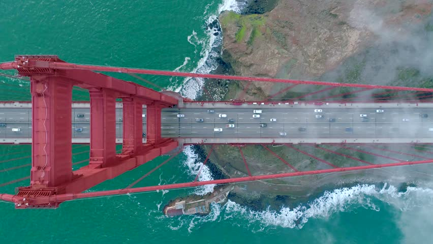 Aerial view of the Golden Gate Bridge. Cloudy fog soaring above the traffic on the red bridge over the green waters of the Pacific Ocean. San Francisco Bay, California, USA. Drone video