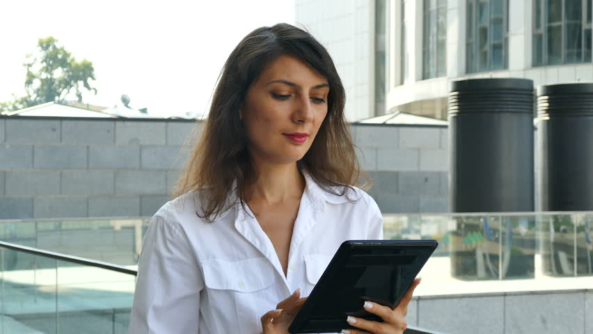 Attractive businesswoman, manager work with tablet in modern city area, steady shot   | Shutterstock HD Video #1028638919