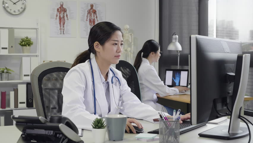 Slow motion excited doctor woman happy smile raised hands arms up while sitting in working office in hospital. girl medical staff share cheerful mood computer monitor to colleague celebrate teamwork | Shutterstock HD Video #1028649521