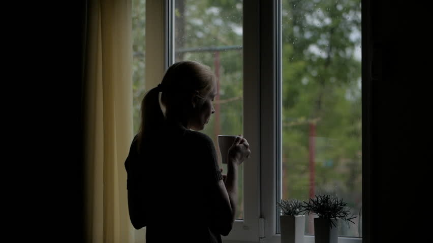 Woman drinks a hot drink from a Cup standing at the window and looks at the rain through the glass.