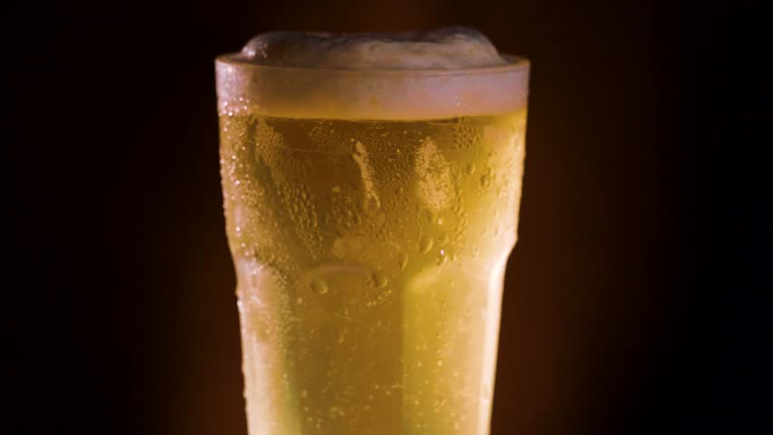 Pouring light beer into a rotating glass. Slow motion foam slides on glass, dark atmosphere.
