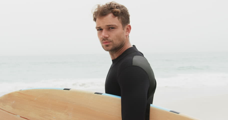 Side view of male surfer standing with surfboard on the beach. He is smiling and looking at camera