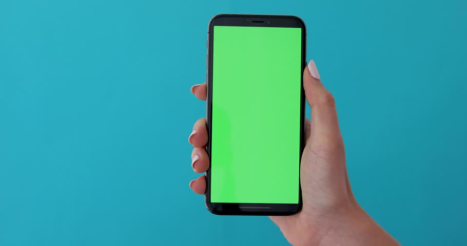 Woman hand holds a smartphone with greeen screen over a blue background. Close up footage of hand only | Shutterstock HD Video #1028678714