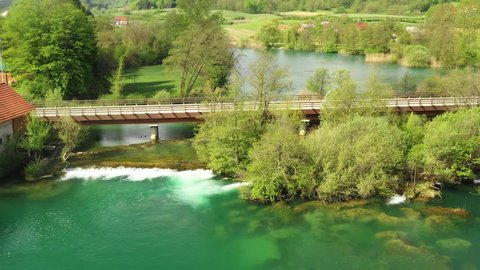 Croatia, road bridge over Mreznica river in Belavici village, panning shot from drone over the water