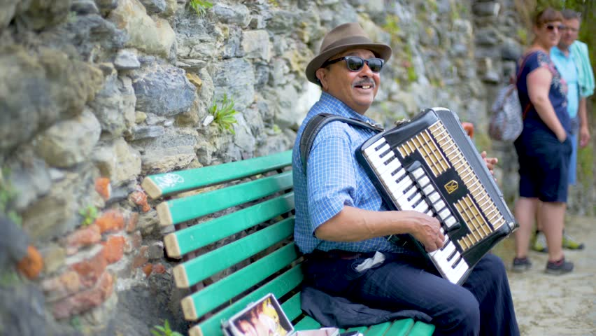 Cinque Terre/Italy - April - 2017:  Street musician with an accordion plays and sings songs on the cinque terre trails in Italy,  Elderly man plays the accordion
