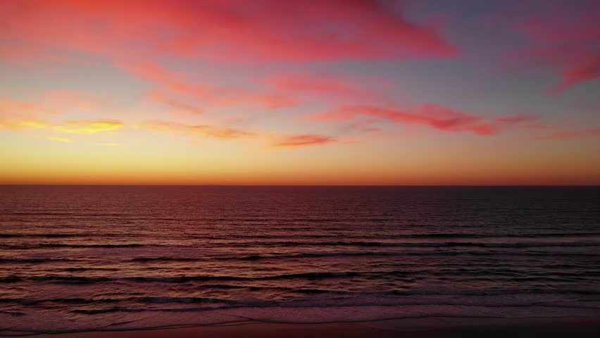 Aerial drone view over the ocean at sunset with neon pink clouds across the dreamy sky. | Shutterstock HD Video #1028706875