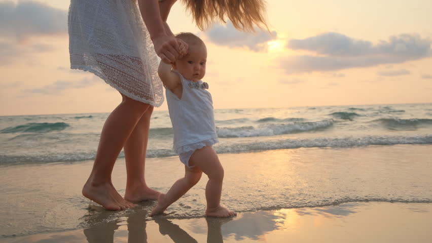 Young Beautiful Woman Walks With Her Little baby On The Seashore At Sunsetg Beautiful Woman Walks With Her Little baby On The Seashore At Sunset. 4k | Shutterstock HD Video #1028707469
