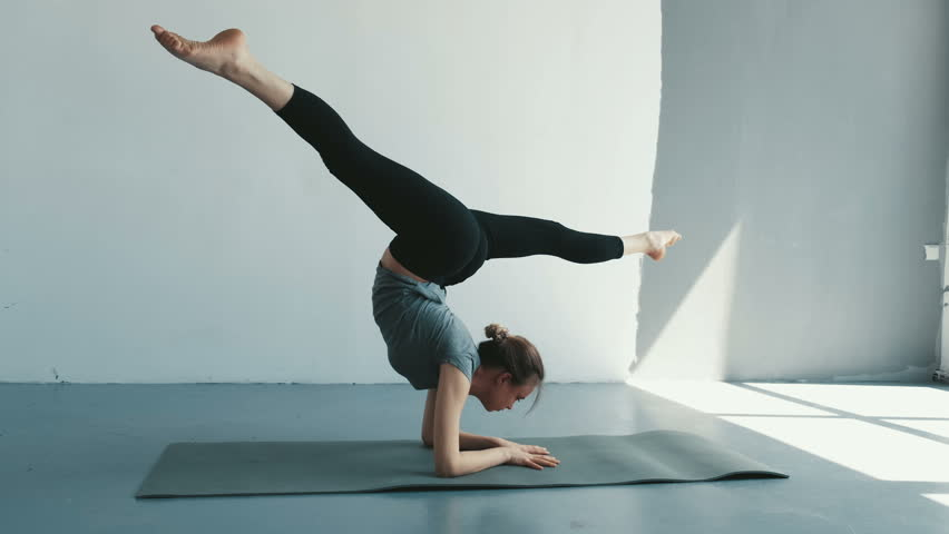 Healthy yoga woman preparing to handstand split pose. Fitness lifestyle exercising in studio stretching beautiful body training | Shutterstock HD Video #1028717327