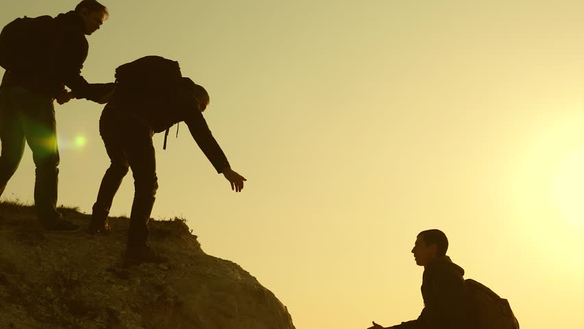 Climbers silhouettes stretch their hands to each other, climbing to the top of hill. travelers climb one after another on the rock. teamwork of business people. A team of businessmen is going to win. | Shutterstock HD Video #1028719838