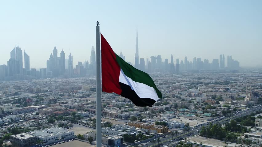 Aerial view of Dubai flag and in background Dubai skyline