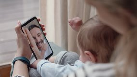 young mother and baby having video chat with father using smartphone waving at little daughter enjoying family connection