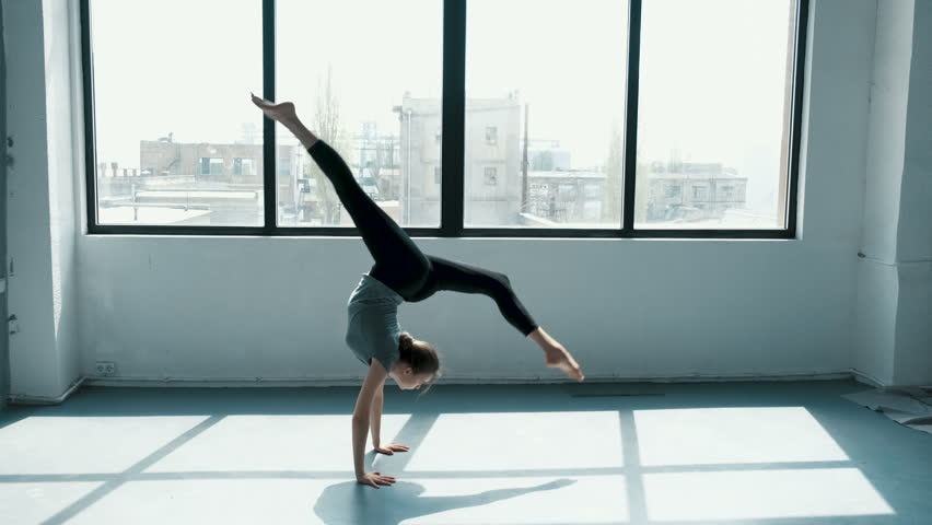 Young female performs a backflip with hands in the dance stodio Flexible woman doing splits in fashion look. View on window sunny day | Shutterstock HD Video #1028752433