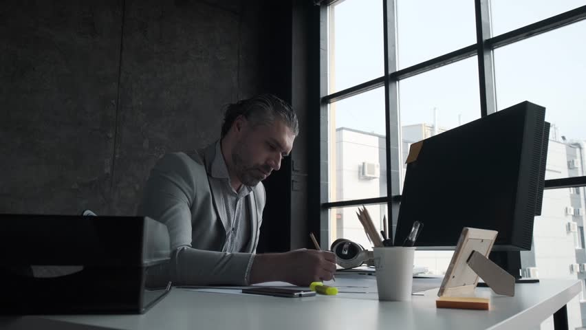 Closeup portrait of middle aged man working in office. Solid business man working with documents at his desk. | Shutterstock HD Video #1028753309