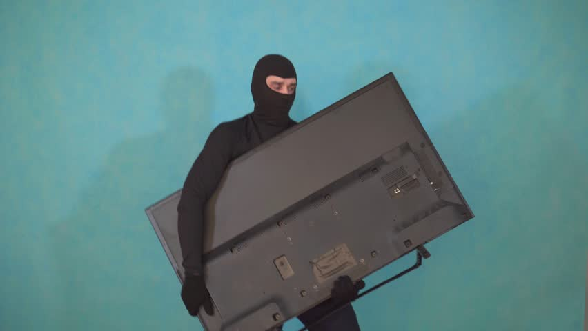 Jolly thief in a Balaclava mask who stole the TV and looks happy and mocking #1028768234