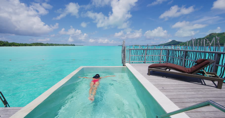 Luxury summer vacation - Woman swimming underwater in bikini in infinity pool at travel hotel resort at ocean beach lagoon. Elegant lady relaxing swimming enjoying holidays at pool. RED SLOW MOTION.