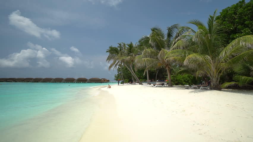 A person far in the distance sunbathes on a tropical beach under gray, stormy skies.   Shutterstock HD Video #1028771798