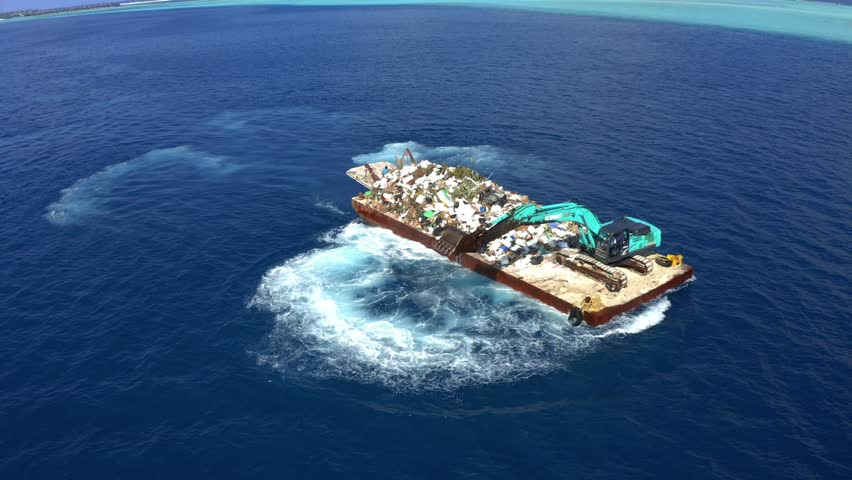 Backhoe on a swimming platform collecting plastic waste from the ocean