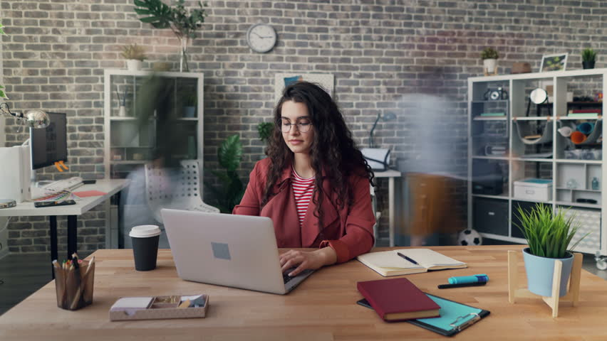 Zoom in time-lapse of attractive young woman hipster using laptop working at project in office while men and women are rushing around. Business and creativity concept.