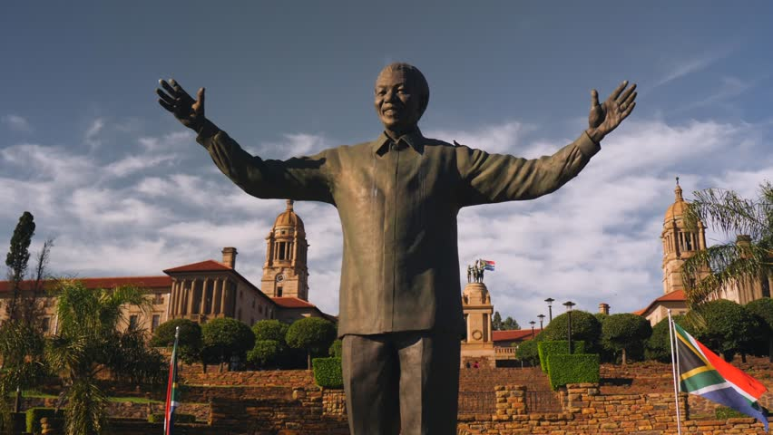Pretoria, South Africa - circa 2019: Dynamic, cinematic wrapping movement of Nelson Mandela statue, below Union Buildings. Statue against buildings, then isolated against sky. Outstretched hands