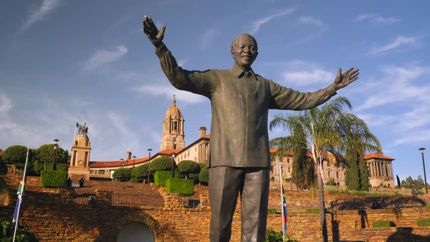 Pretoria, South Africa - circa 2019: Massive statue of Nelson Mandela towers over tourists at Union Buildings. Friendly welcoming posture on a beautiful sunny, summer day