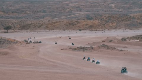 Column of a Quad Bike Rides through the Desert in Egypt on backdrop of the Mountains. Driving ATVs. Adventures of desert off-road on ATVs. Safari excursion. Tourist ride on quads through the desert in