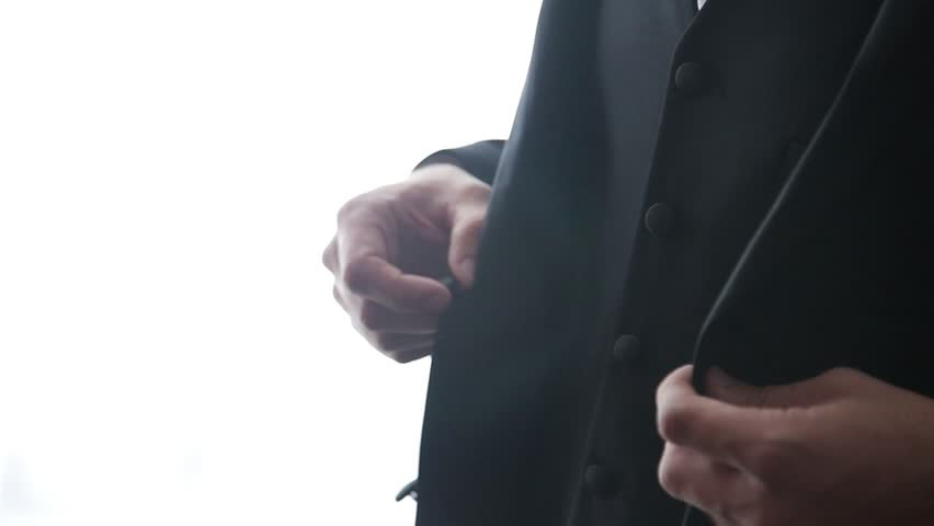 Buttoning a jacket. Stylish man in a suit fastening buttons on his jacket preparing to go out. Close up | Shutterstock HD Video #1028813621