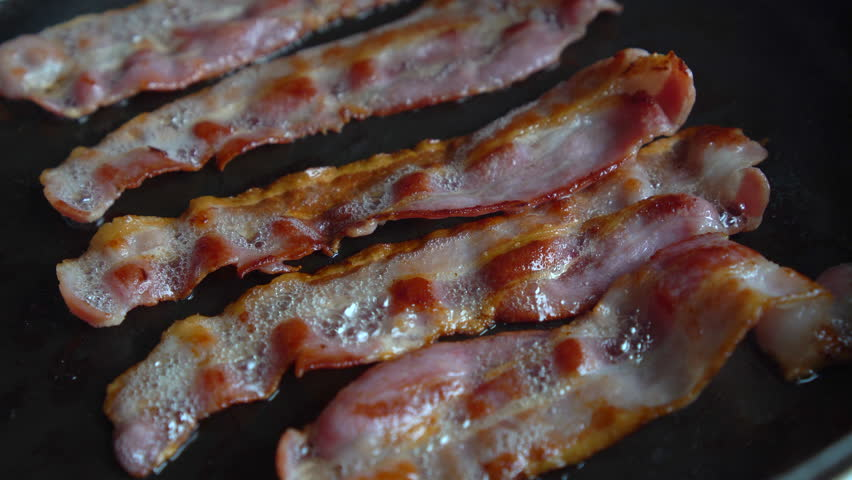 Man Chef cooking for breakfast, turning an amazing crispy bacon, rich in fat and colour, sizzling and smoking in a hot pan. #1028814194