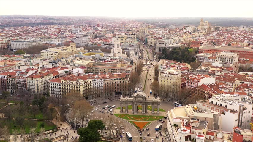 Busy Puerta de Alcalá in Madrid. Cars are driving on the street and pedestrians are entering and leaving the park El Retiro. The scenery is shown in an aerial shot on a semi cloudy day. Royalty-Free Stock Footage #1028815688
