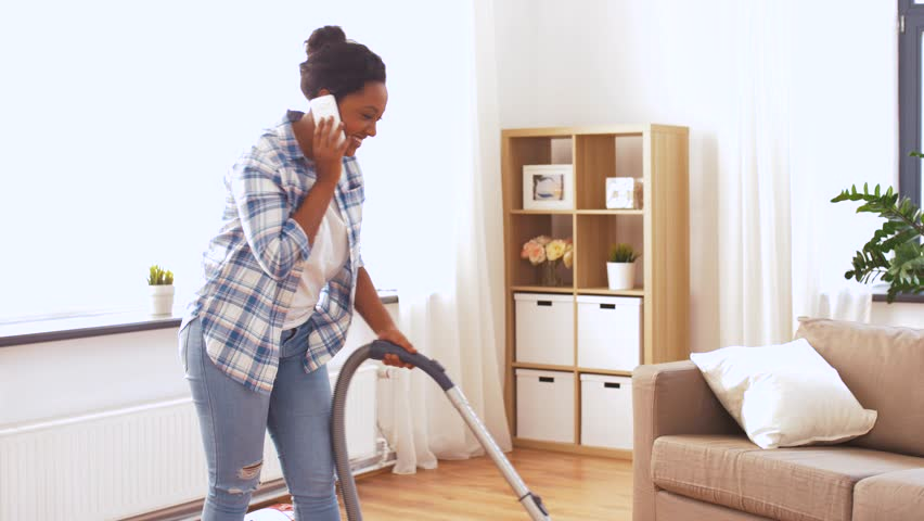 people, housework and housekeeping concept - happy african american woman with vacuum cleaner calling on smartphone at home #1028826263