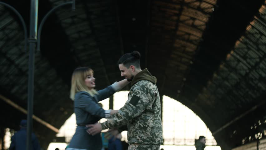 Happy Caucasian soldier throws his backpack to embrace his beloved girlfriend, wife, sister on a railway station. Army soldier returning home to the embrace of his wife. True love, happy reunion