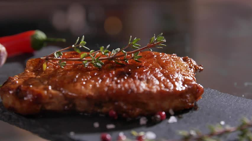 Close up rotation view of cooked juicy appetite beef steak on wooden board with a sprig of rosemary. Professional cooking, European cuisine, restaurant dish, chef's compliment