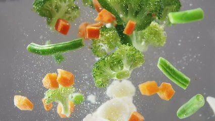 Fresh vegetables falling under water on white background in slow motion. Salad, healthy food, delicious. Diet, vegetarian lifestyle, eco products, organic. Vitamins. Close up view