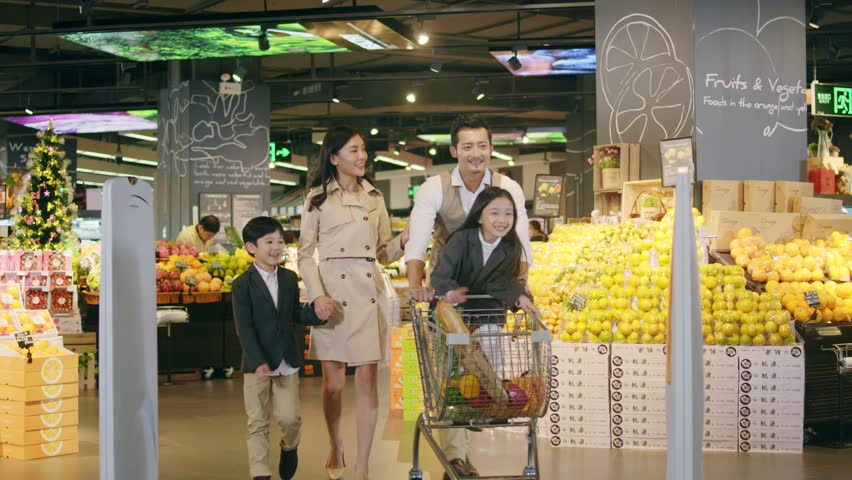 Shenzhen, Guangdong, China - November 30, 2019: An Asian family with two children is seen talking while leaving an Ole Supermarket store with a shopping cart full of groceries.