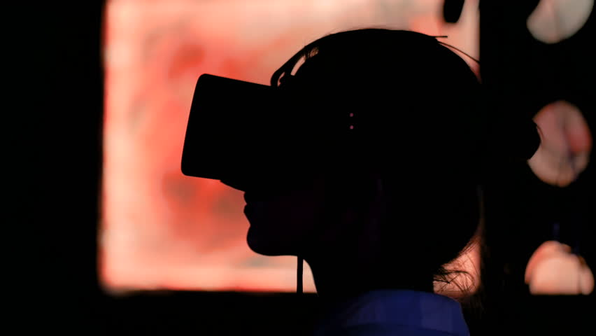 Woman using virtual reality headset and looking around at interactive technology exhibition. VR, augmented reality, digital art, futuristic, interactive, immersive and entertainment concept | Shutterstock HD Video #1028830373