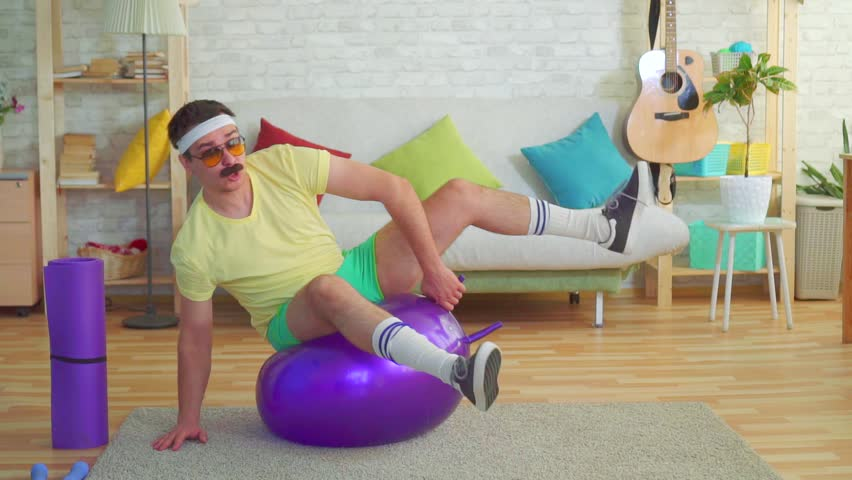 Funny young man with a mustache from the 80s trains and absurdly falls off a fitness ball in his house slow mo