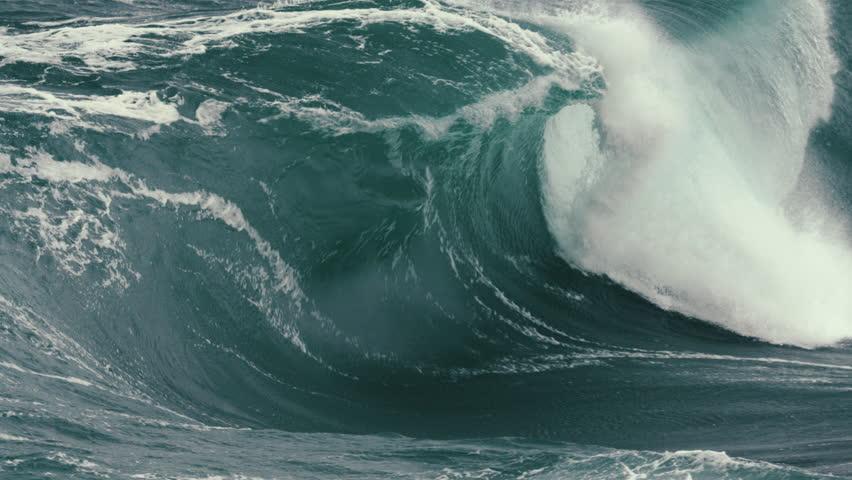 Foamy wave breaking in slow motion close to rocks. Royalty-Free Stock Footage #1028860163