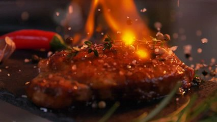 Slow-motion footage of throwing salt and pepper on fresh beef meat on ignited pan.