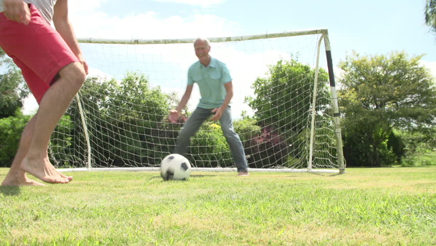 Grandson playing football with father and grandfather - he scores goal.Shot on Sony FS700 at frame rate of 25fps   Shutterstock HD Video #10288919