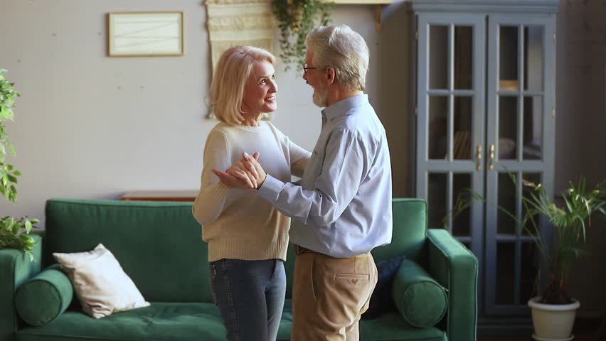 Happy romantic old senior couple dancing waltz in modern living room, loving mature spouses enjoy tender moment in slow dance, elder aged family grandparents relaxing together celebrating anniversary Royalty-Free Stock Footage #1028899868