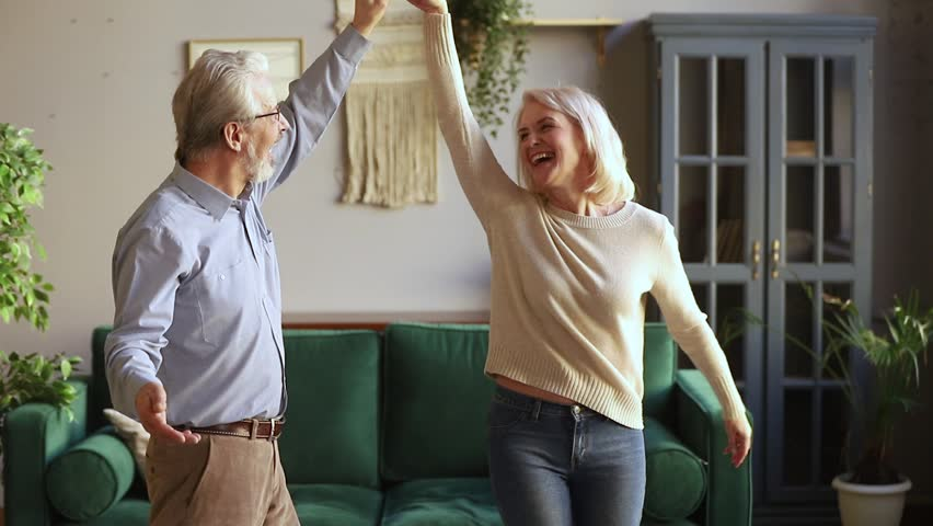 Happy old senior romantic couple dancing in modern living room, loving elder husband holding middle aged wife hand spinning around having fun at home, aged family grandparents relaxing together Royalty-Free Stock Footage #1028899871