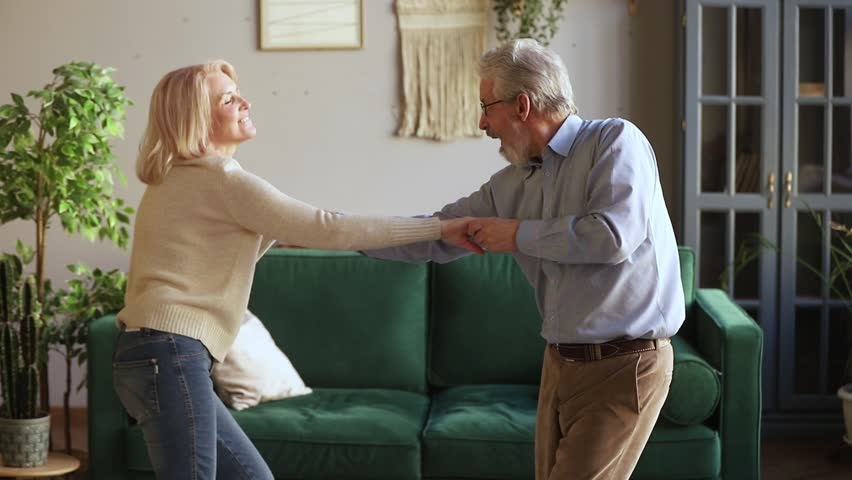 Happy active aged senior couple dancing having fun at home together, funky carefree old mature man and woman holding hands jumping to music enjoy weekend or celebrating anniversary in living room Royalty-Free Stock Footage #1028899886