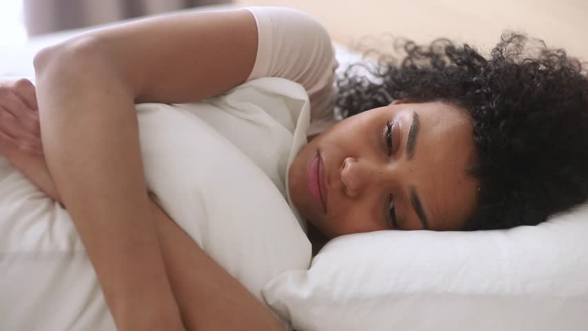 Depressed upset african american woman feeling sad lonely lying in bed alone trying to sleep thinking of problem, frustrated mixed race black girl suffer from anxiety and insomnia in bedroom