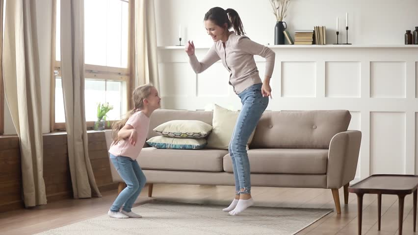 Happy family young mom babysitter having fun with cute little kid girl dancing in living room, carefree mother with child daughter laughing jumping enjoying funny activity playing together at home #1028899976