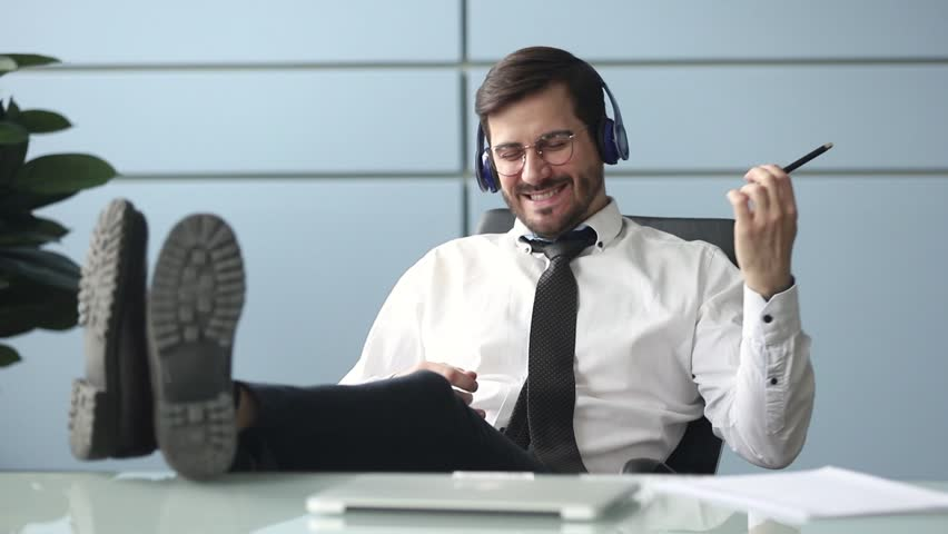 Happy funky businessman relaxing wearing wireless headphones listening to music pretending playing guitar at workplace, funny male worker enjoy favorite track having fun during work break in office | Shutterstock HD Video #1028900018