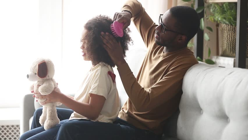 Loving black father doing brushing afro hair of cute little kid daughter talking bonding sitting on sofa at home, caring single african dad babysitter helping child girl with hairstyle in the morning Royalty-Free Stock Footage #1028900024
