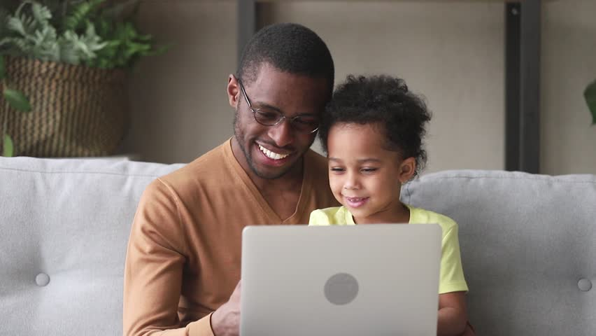 Happy black father teach cute kid son learn to read use laptop at home for children education, smiling caring african dad and little child boy looking at computer screen do online shopping at home